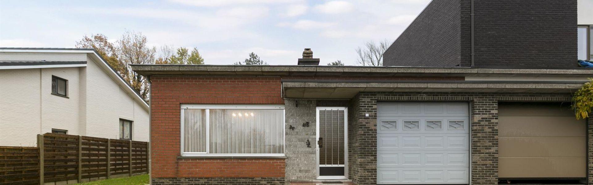 De op te frissen bungalow bevindt zich in een rustige doodlopende straat maar is wel dicht bij het centrum van St-Pauwels, vlotte ontsluiting via E49 en E17. Er is een inpandige garage die connecteert met de inkomhal. De leefruimte met open haard is heel
