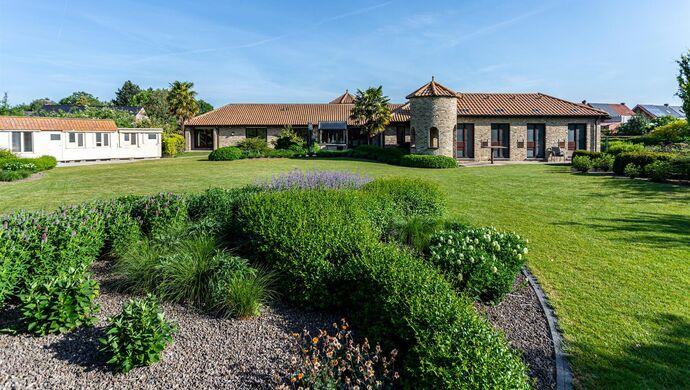 Laat je betoveren door deze exclusieve Spaanse laagbouwvilla, omringd door natuur op het prachtige domein van 8940m². Een grote automatische poort aan de straatkant (47m breedte) geeft toegang tot de ruime oprit. De lichtrijke villa in Spaanse stijl date
